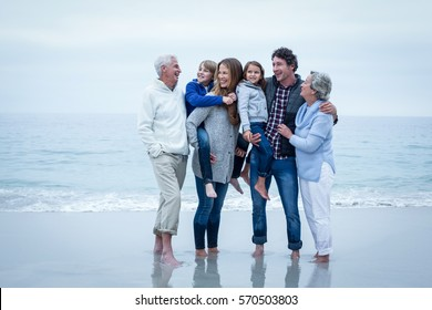 Full length of cheerful family standing at sea shore against sky