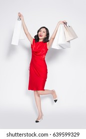 Full length of cheerful fashionable asian woman wearing a red dress with shopping bags