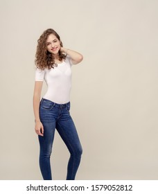 Full length cheerful girl in studio. White T-shirt, jeans, curly hair.