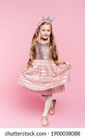 full length of cheerful little girl in dress and crown posing on pink