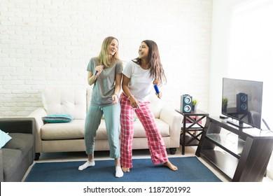 Full length of cheerful women singing karaoke and dancing in living room