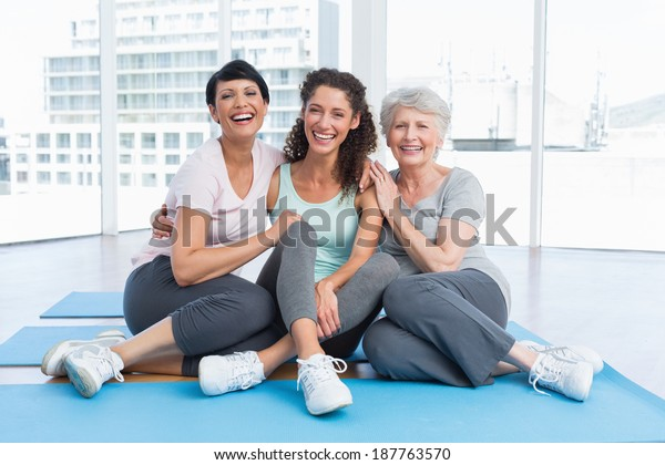 Full length of cheerful women sitting in the yoga class
