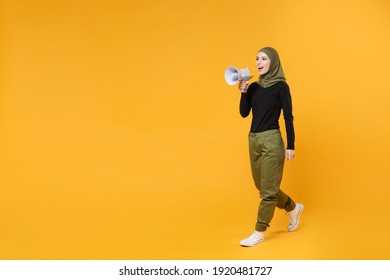 Full length of cheerful young arabian muslim woman in hijab black green clothes screaming in megaphone looking aside isolated on yellow background studio portrait. People religious lifestyle concept