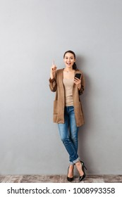 Full length of a cheerful young asian woman pointing finger up while standing and holding mobile phone over gray background