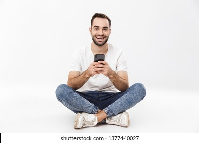 Full length of a cheerful young man sitting with legs crossed isolated over white background, using mobile phone