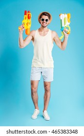 Full length of cheerful young man holding two water guns over blue background