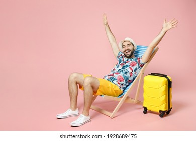Full length of cheerful young traveler tourist man in summer clothes hat sit on deck chair rising spreading hands isolated on pink background. Passenger travel on weekend. Air flight journey concept