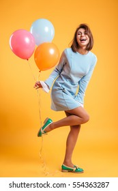 Full length of cheerful young woman with balloons standing and laughing