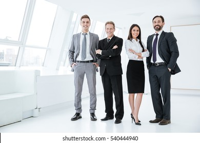 Full length confident business team stands in office