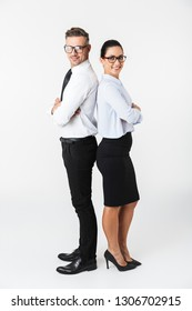 Full length of a confident colleagues couple wearing formal clothing standing isolated over white background, arms folded