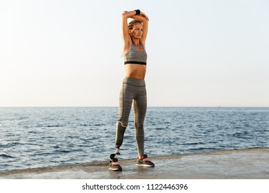 Full length of confident disabled athlete woman with prosthetic leg doing stretching exercises while standing at the beach