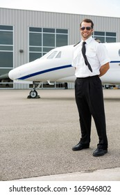 Full length of confident pilot with private jet in background