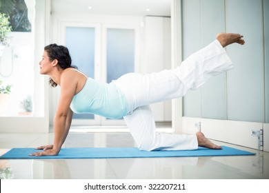Full length of confident pregnant woman performing yoga on mat at fitness studio