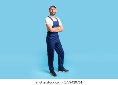Full length confident professional handyman in overalls standing with crossed hands, smiling at camera. Profession of service industry, house repair. indoor studio shot isolated on blue background