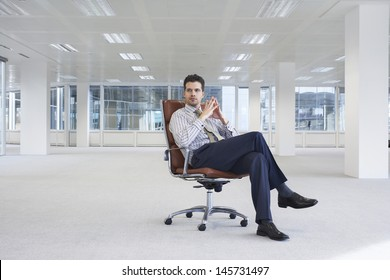 Full length of confident young businessman on chair in empty office space