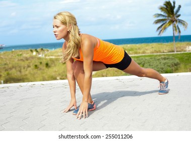 Full length of confident young woman stretching at beach