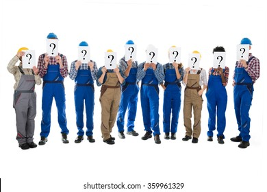 Full length of construction workers hiding faces with question mark signs against white background