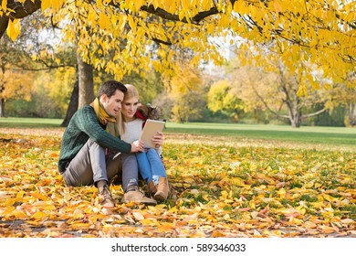 Full length of couple using tablet PC in park during autumn