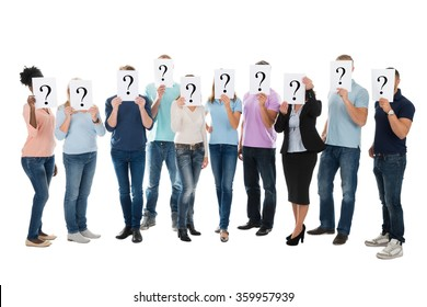 Full length of creative business team hiding faces with question mark signs over white background