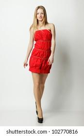 Full length of cute female fashion model posing in red dress