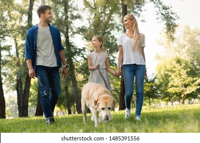 Full length of cute smiling little girl and her parents walking in park with dog and looking on each other