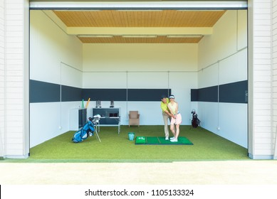 Full length of a dedicated golf coach using modern equipment, while teaching a young woman the correct movement for striking the ball as a professional player