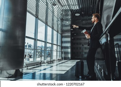 Full length of a delighted adult businessman pointing in the window while waiting for his flight at the airport