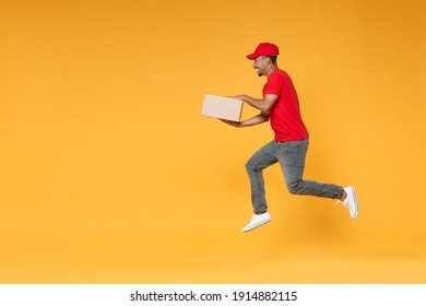 Full length delivery employee african man in red cap blank print t-shirt uniform work courier service on quarantine covid-19 virus concept jump hold cardboard box isolated on yellow background studio