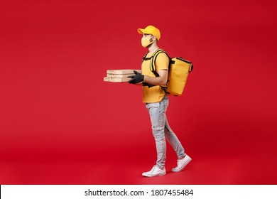 Full length delivery employee man in yellow cap face mask gloves t-shirt thermal food bag backpack hold cardboard pizza flatbox work courier service in quarantine covid-19 isolated on red background