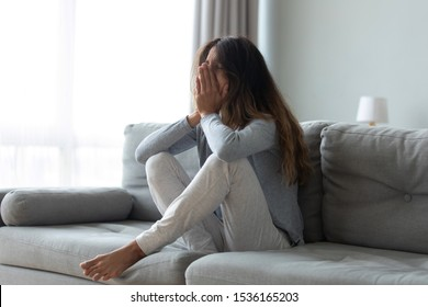 Full length desperate grieving millennial biracial woman sitting on couch at home, crying of beloved loss or relative death. Stressed young mixed race girl need professional psychological help.