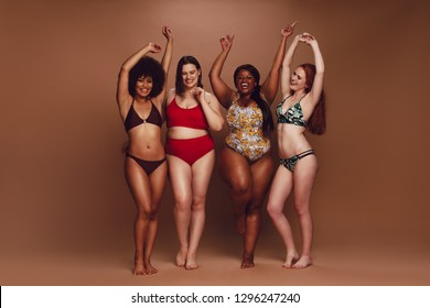 Full length of different size women in bikinis dancing together over brown background. Multi-ethnic women in swimwear enjoying themselves.
