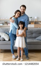 Full length diverse multi-ethnic family married couple wife husband little daughter embracing standing together in living room smiling looking at camera at new modern home feels happy and satisfied