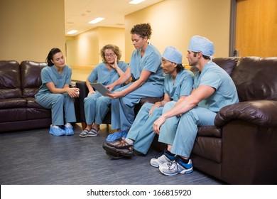 Full length of doctors and nurses using digital tablet in hospital's waiting room