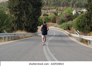 Full length Elderly Man in gray shorts and black shirt sportswear running on road near the nature-blossom tree and flowers.