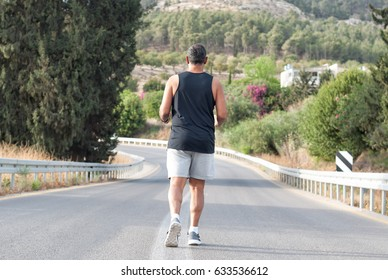 Full length Elderly Man in gray shorts and black shirt sportswear running on road near the nature-blossom tree and flowers.Back view.Close-up.Jog workout,healthy lifestyle,well-being .Soft focus.