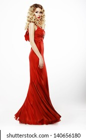 Full Length of Elegant Lady in Red Satiny Dress. Frizzy Blond Hair. Luxury