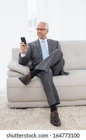 Full length of an elegant mature businessman text messaging on sofa in living room at home