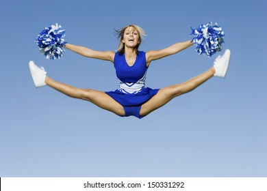 Full length of excited cheerleader with pompoms doing splits against blue sky