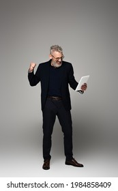 full length of excited middle aged businessman with grey hair looking at digital tablet and rejoicing on grey