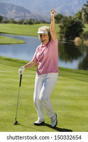 Full length of excited senior woman with golf club on course