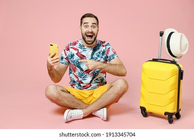 Full length excited traveler tourist man sit on floor point index finger on mobile cell phone booking hotel taxi isolated on pink background. Passenger travel on weekend. Air flight journey concept - Shutterstock ID 1913345704