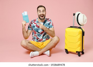Full length of excited traveler tourist man sit on floor near suitcase pointing index finger on passport tickets isolated on pink background. Passenger travel on weekend. Air flight journey concept