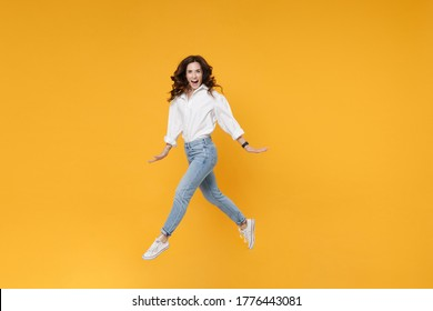 full length Excited young business woman in white shirt posing isolated on yellow background in studio. Achievement career wealth business concept. Mock up copy space. Jump spreading hands and legs