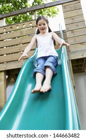 Full length of excited young girl playing on slide in park