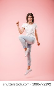 Full length of an excited young woman jumping and celebrating success isolated over pink background