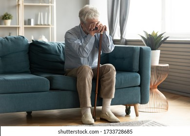Full length exhausted disabled middle aged old man resting on sofa, leaning on walking cane, suffering from depression alone at home. Upset hoary elder senior grandfather tired of hard rehabilitation.