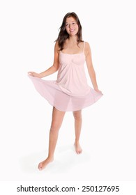 Full length fashion portrait of a beautiful young woman dancing barefoot, isolated in front of white studio background