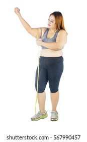 Full length of fat woman measuring her arm by using measuring tape, isolated on white background