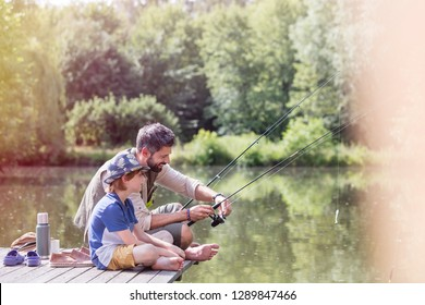 Full length of father assisting son fishing in lake while sitting on pier