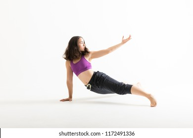 Full length of female contemporary dancer showing dance moves on white background